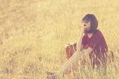 Frau mit koffer auf wiese — Stockfoto