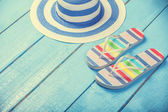Beach slippers and hat on blue wood — Stock Photo