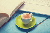 Cup of coffe with laptop and book on blue wooden table. — Stock Photo