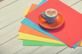 Cup of coffee and color paper on wooden table. — Stock Photo