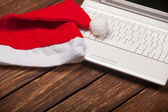 Laptop and chirstmas hat — Stock Photo