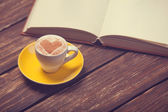 Cup of coffee with heart shape and book on wooden table. — Stock Photo