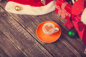 Cup of coffee with heart shape with christmas gifts. — Stock Photo