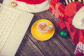 Cup of coffee with heart shape, laptop and christmas gifts. — Stock Photo