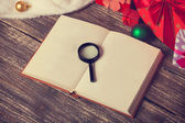 Loupe and book on christmas gifts background — Stock Photo