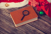 Book and loupe with chirstmas gifts — Stock Photo
