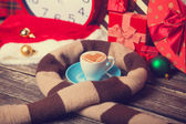 Cup of coffee with heart shape, scarf and christmas gifts. — Stock Photo