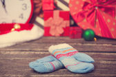 Mittens and christmas gifts around. — Stock Photo