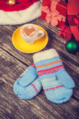 Cup of coffee with heart shape, mittens and christmas gifts. — Stock Photo