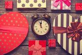 Retro alarm clock and christmas gifts around — Stock Photo