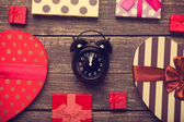 Retro alarm clock and christmas gifts around — Stock Photo