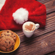Cookie and cup of coffee with santa's hat on wooden table. — Zdjęcie stockowe #51054537