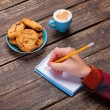Female hand writing something in note near cookie and cup of cof — Stock Photo #51054801