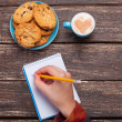 Female hand writing something in note near cookie and cup of cof — Stock Photo #51054809