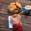 Female hand writing something in note near cookie and cup of cof — Stock Photo #51054811