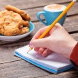 Female hand writing something in note near cookie and cup of cof — Stock Photo #51054817