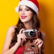 Beautiful brunette girl in christmas hat with camera on yellow b — Stock Photo #51055057