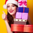 Beautiful brunette girl in christmas hat with gift on yellow bac — Stock Photo #51055071