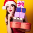 Beautiful brunette girl in christmas hat with gift on yellow bac — Stock Photo #51055077