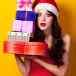 Beautiful brunette girl in christmas hat with gift on yellow bac — Stock Photo #51055089