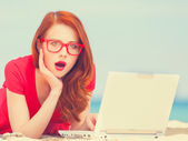 Redhead girl in the glasses with notebook on the beach — Stock Photo