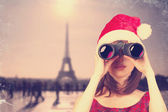 Girl with binocular and christmas hat and parisian background. — Stock Photo