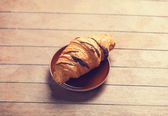 French croissant on a wooden table — Stock Photo