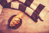 French croissant and scarf on a wooden table — Stock Photo