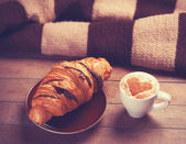 Francês croissant e xícara de café em uma mesa de madeira — Foto Stock