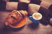Francés croissant y café en una mesa de madera — Foto de Stock