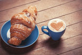 French croissant and cup of coffee on a wooden table — Stock Photo