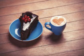 Cake and cup of coffee on a wooden table. — Stock Photo