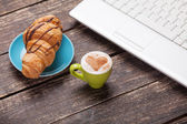 Croissant and cup of coffee with laptop on wooden table. — Foto de Stock