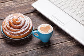 Bun and cup of coffee with laptop on wooden table. — Stock Photo