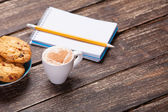 Cookie and cup with coffee, pencil and notebook. — Stock Photo