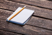 Notebook and pencil on wooden table. — Stock Photo