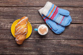Gloves and cup of coffee on wooden table. — Stock Photo
