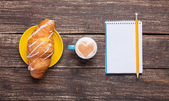 Croissant and cup of coffee with notebook on wooden table. — Stock Photo