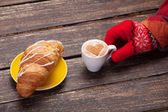 Female hand in glove holding cup of coffee near croissant on woo — Foto Stock