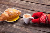 Female hand in glove holding cup of coffee near croissant on woo — 图库照片