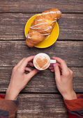 Female hands with cup of coffee and croissant on wooden table. — Stock Photo
