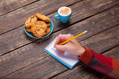 Female hand writing something in note near cookie and cup of cof — Photo