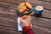 Female hand writing something in note near cookie and cup of cof — Stock Photo