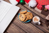 Laptop and cookies wuth cup of coffee near christmas gifts. — Stock Photo