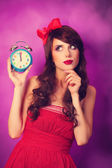 Surprised girl with alarm clock on violet background. — Stock Photo