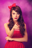 Surprised girl in red dress on violet background. — Stock Photo