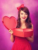 Красивая девушка брюнетка с подарком форму сердца на фиолетовый му — Стоковое фото
