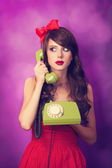 Beautiful brunette girl with telephone on violet background. — Stock Photo