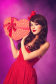 Beautiful brunette girl with heart shape gift on violet backgrou — Stock Photo
