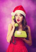 Beautiful brunette girl in christmas hat with green telephone on — Stock Photo